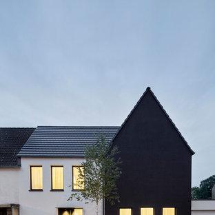 Источник вдохновения для домашнего уюта: маленький, двухэтажный частный загородный дом в стиле модернизм с облицовкой из цементной штукатурки, двускатной крышей и черепичной крышей