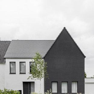 Imagen de fachada de casa minimalista, pequeña, de tres plantas, con revestimiento de estuco, tejado a dos aguas y tejado de teja de barro