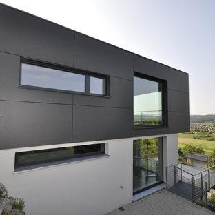 Ejemplo de fachada negra, contemporánea, de tamaño medio, de dos plantas, con tejado plano y revestimientos combinados