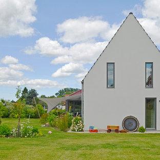 Diseño de fachada beige, escandinava, de tamaño medio, de dos plantas, con tejado a dos aguas