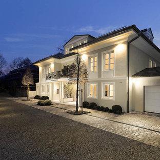 Drei- oder mehrstöckiges, Großes, Beigefarbenes Klassisches Einfamilienhaus mit Putzfassade und Walmdach in München