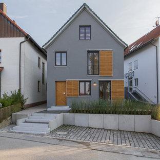 Exemple d'une façade de maison grise scandinave de taille moyenne et à deux étages et plus avec un revêtement en stuc et un toit à deux pans.