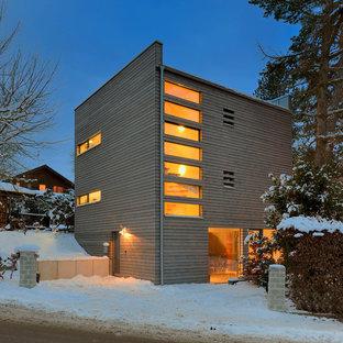 Small scandinavian three-story wood flat roof idea in Munich