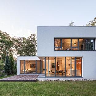 Réalisation d'une façade de maison blanche design de taille moyenne et à un étage avec un toit plat et un revêtement en stuc.