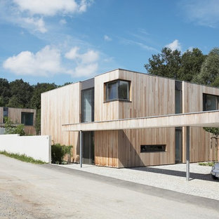 This is an example of a mid-sized modern two-storey brown exterior in Dortmund with wood siding and a flat roof.