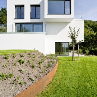 Foto de fachada blanca, moderna, grande, a niveles, con tejado plano y revestimiento de estuco