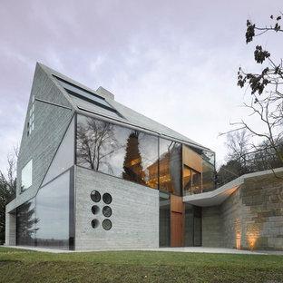 Idéer för att renovera ett mellanstort funkis grått betonghus, med tre eller fler plan och sadeltak