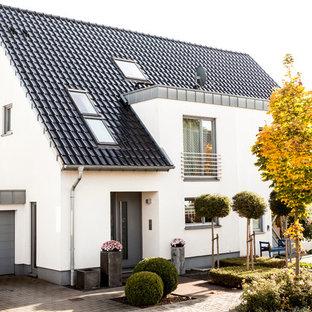 Свежая идея для дизайна: белый, двухэтажный дуплекс среднего размера в современном стиле с двускатной крышей, облицовкой из цементной штукатурки и черепичной крышей - отличное фото интерьера