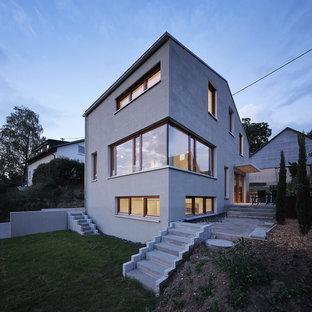 Großes, Dreistöckiges, Graues Modernes Einfamilienhaus mit Putzfassade und Satteldach