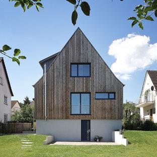 Dreistöckiges, Beigefarbenes, Mittelgroßes Modernes Einfamilienhaus mit Mix-Fassade und Satteldach