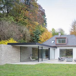 Ejemplo de fachada de casa blanca, moderna, pequeña, de una planta, con revestimientos combinados