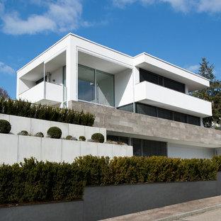 Modelo de fachada blanca, minimalista, grande, de tres plantas, con tejado plano