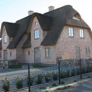 Mid-sized rustic brick duplex exterior idea in Other