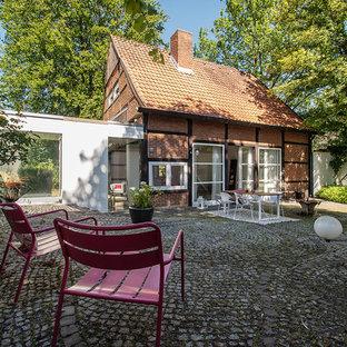 Mittelgroßes, Zweistöckiges, Rotes Landhausstil Einfamilienhaus mit Backsteinfassade, Satteldach und Ziegeldach in Sonstige
