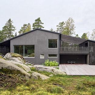 Ejemplo de fachada gris, nórdica, de tamaño medio, a niveles, con revestimiento de estuco y tejado a dos aguas
