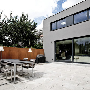 Modelo de fachada gris, contemporánea, de tamaño medio, de dos plantas, con tejado plano