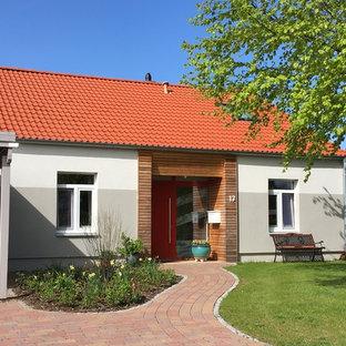 Imagen de fachada de casa actual, pequeña, de una planta, con revestimiento de estuco, tejado a dos aguas y tejado de teja de barro