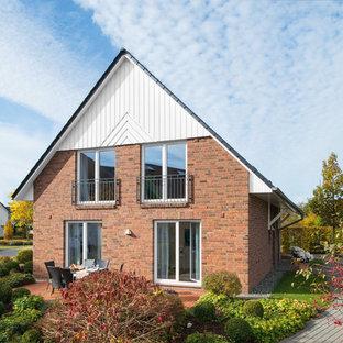 Mittelgroßes, Braunes, Zweistöckiges Landhausstil Einfamilienhaus mit Backsteinfassade, Satteldach und Ziegeldach in Sonstige