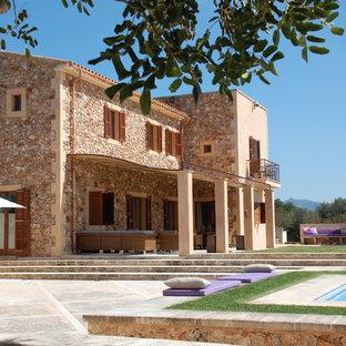 Ejemplo de fachada beige, mediterránea, grande, de dos plantas, con revestimiento de piedra y tejado a dos aguas