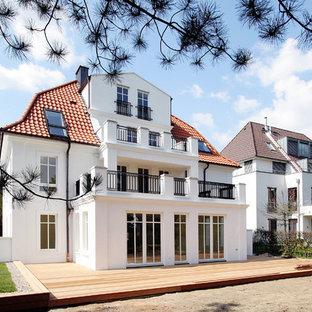 Esempio della facciata di un appartamento bianco classico a tre o più piani di medie dimensioni con rivestimento in stucco, tetto a padiglione e copertura in tegole