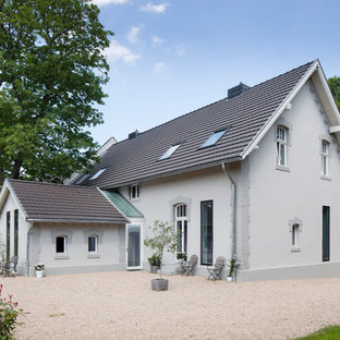Design ideas for a large scandinavian two-storey grey exterior in Dusseldorf with a gable roof.
