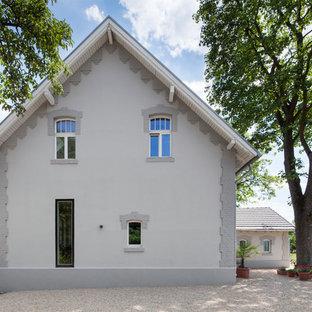 Ejemplo de fachada gris, escandinava, grande, de dos plantas, con revestimientos combinados y tejado a dos aguas