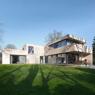 Foto della facciata di una casa unifamiliare ampia beige contemporanea a due piani con rivestimento in mattoni e tetto piano