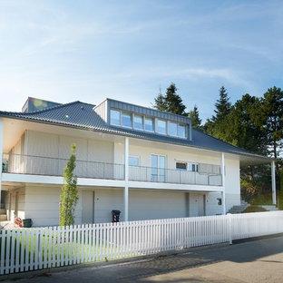 ミュンヘンのコンテンポラリースタイルのおしゃれな家の外観 (漆喰サイディング、半切妻屋根、戸建、瓦屋根) の写真