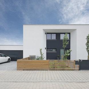 Esempio della facciata di una casa unifamiliare bianca contemporanea a due piani di medie dimensioni con rivestimento in stucco e tetto piano
