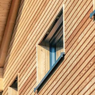 Foto de fachada de casa contemporánea, de tamaño medio, de dos plantas, con revestimiento de madera, tejado a dos aguas y tejado de teja de barro