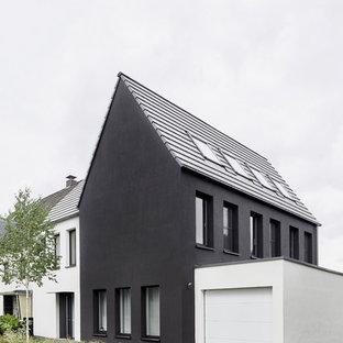 Inredning av ett modernt svart hus, med stuckatur, sadeltak och tak med takplattor