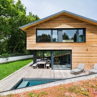 Неиссякаемый источник вдохновения для домашнего уюта: двухэтажный фасад дома среднего размера коричневого цвета в современном стиле с облицовкой из дерева и двускатной крышей