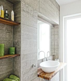 Новый формат декора квартиры: маленький туалет в современном стиле с серой плиткой, цементной плиткой, белыми стенами, полом из цементной плитки, настольной раковиной, столешницей из дерева и серым полом