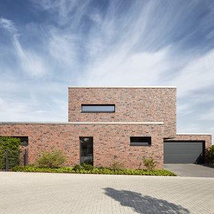 Mittelgroßes, Zweistöckiges, Rotes Modernes Einfamilienhaus mit Backsteinfassade und Flachdach in Düsseldorf