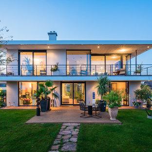 Неиссякаемый источник вдохновения для домашнего уюта: двухэтажный, стеклянный, белый дом среднего размера в современном стиле с плоской крышей