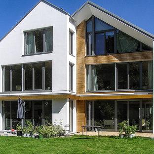 Esempio della facciata di una casa grande bianca classica a tre piani con rivestimenti misti e tetto a capanna