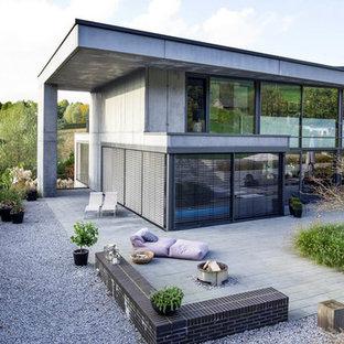 На фото: большой, двухэтажный, серый многоквартирный дом в современном стиле с облицовкой из бетона, плоской крышей и металлической крышей с