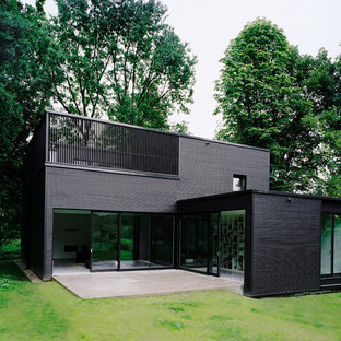 Inspiration for a mid-sized modern two-storey black exterior in Berlin with mixed siding and a flat roof.