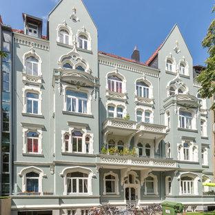 ハノーファーのトラディショナルスタイルのおしゃれな三階建ての家 (緑の外壁、切妻屋根、アパート・マンション、瓦屋根) の写真