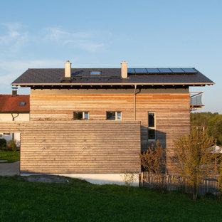 Foto de fachada de casa nórdica, de tamaño medio, a niveles, con revestimiento de madera, tejado a dos aguas y tejado de teja de barro