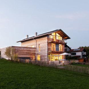 Diseño de fachada de casa nórdica, de tamaño medio, a niveles, con revestimiento de madera, tejado a dos aguas y tejado de teja de barro