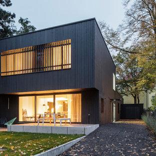 Mittelgroßes, Zweistöckiges, Braunes Modernes Einfamilienhaus mit Holzfassade und Flachdach in Berlin