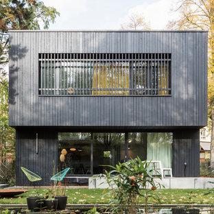 Zweistöckiges, Schwarzes, Mittelgroßes Modernes Haus mit Holzfassade und Flachdach in Berlin