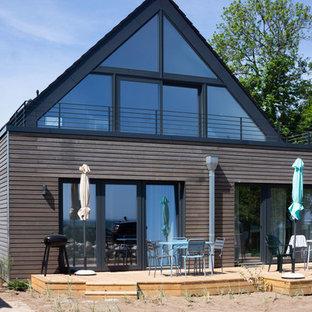 Свежая идея для дизайна: большой, двухэтажный, деревянный, серый многоквартирный дом в скандинавском стиле с двускатной крышей и черепичной крышей - отличное фото интерьера