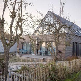 Minimalistisk inredning av ett stort grått hus, med två våningar, sadeltak och tak med takplattor
