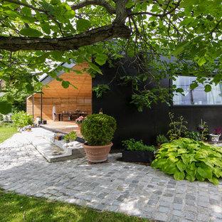 Ejemplo de fachada negra, nórdica, pequeña, de una planta, con tejado plano