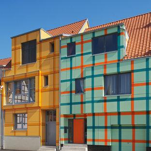 Cette image montre une façade de maison orange design à deux étages et plus et de taille moyenne avec un toit à deux pans.
