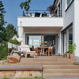Inspiration för ett stort funkis vitt hus, med två våningar, stuckatur, sadeltak och tak med takplattor