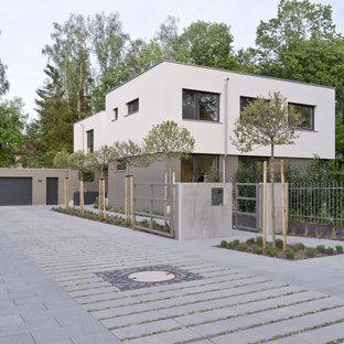 Foto de fachada de casa negra, moderna, grande, de dos plantas, con revestimiento de estuco, tejado plano y techo verde