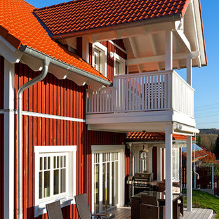 Mid-sized danish red one-story wood exterior home photo in Frankfurt with a tile roof